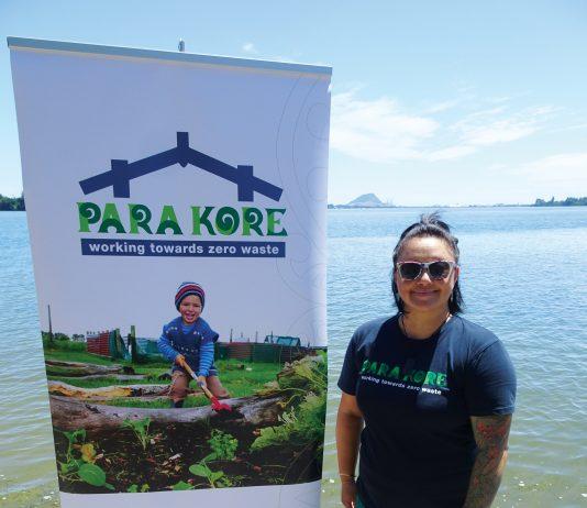 A maori woman standing next ot a sign for Para Kore Marae Incorporated Zero waste initiative