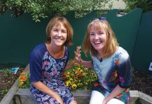 Photograph of two women sitting on a planter box at the Children's Garden preschool