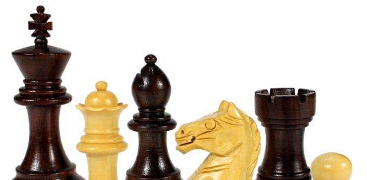 a row of assorted wooden chess pieces