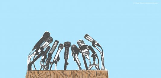 A picture of a lectern covered in microphones on a blue background
