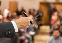 picture of a hand holding a gavel in front of a room of people