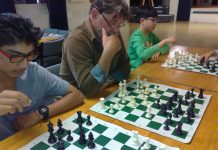 three people sitting in a row playing three different games of chess