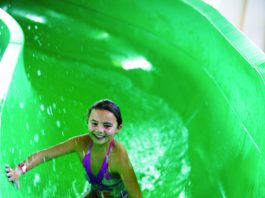 two children inside a green hydro slide