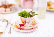 Photograph of a pink teacup and saucer that is filled with green leaves on a white table cloth