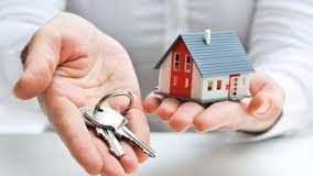 close up picture of investor holding a small house in one hand and a set of keys in their other hand