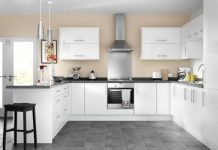 a picture of a showroom kitchen with white cupboards and a steel rangehood