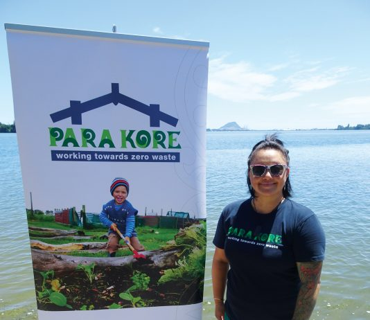 A maori woman standing next ot a sign for Para Kore Marae Incorporated Zero waste initiative