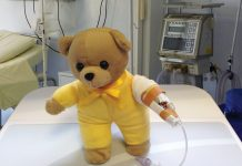 Picture of hospital teddy bear in yellow shirt with a drip on its arm sitting on a hospital bed