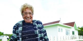 photograph of Dene Reweti (92) standing in front of the all saints church
