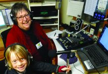 picture of a female DJ and a child in the broadcasting booth of the Historic Village Radio station