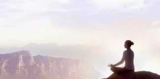 picture of a woman sitting on a rock meditating