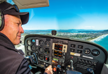 Paul Ensor at the controls of his plane flying over Tauranga coastline